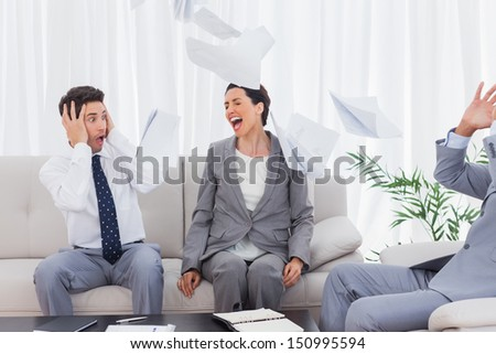 Businessmen shocked at colleague screaming and throwing papers on the sofa in office - stock photo