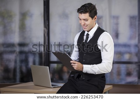 businessmen sitting on desk in his office holding clipboard