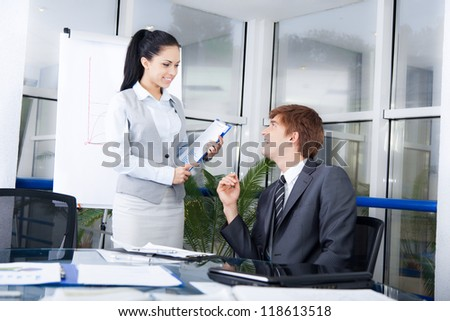 Businessmen smile talking to businesswoman colleague, businesspeople executive secretary and boss at desk in office boardroom during conference meeting, business people communicate