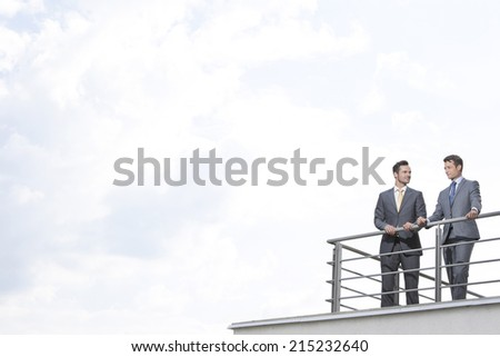 Businessmen standing at terrace railings against cloudy sky - stock photo