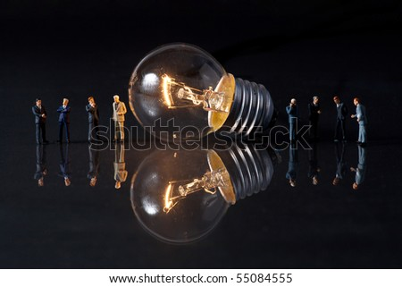 businessmen thinking, standing in front of a bulb - stock photo