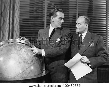 Businessmen with globe - stock photo