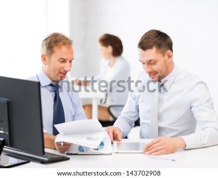 businessmen with notebook and tablet pc discussing graphs on meeting - stock photo