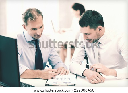 businessmen with notebook discussing graphs on meeting - stock photo