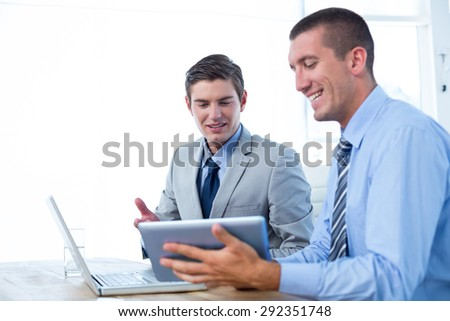 Businessmen working together with laptop and tablet in an office - stock photo