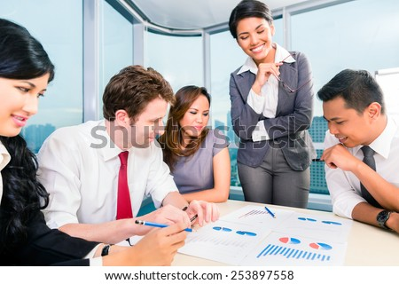 Businesspeople anaylzing graph in office - stock photo