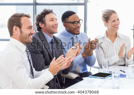 Businesspeople applauding while in a meeting at office - stock photo