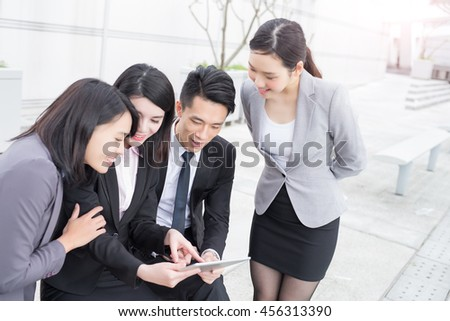 businesspeople are looking tablet pc and meeting in hongkong, asian
