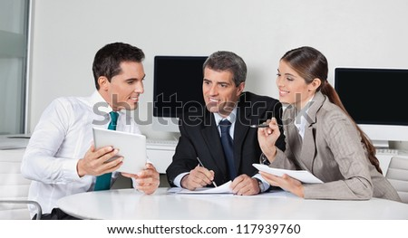 Businesspeople at a meeting with tablet computer in the office - stock photo