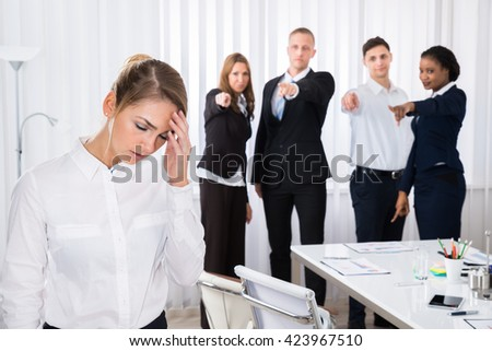 Businesspeople Blaming Frustrated Female Colleague In Office - stock photo