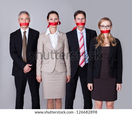 Businesspeople bound by red tape around their mouths standing in a row unable to speak or divulge information - stock photo