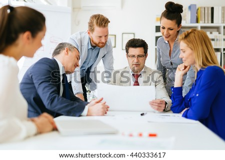 Businesspeople collaborating and talking through new ideas in office