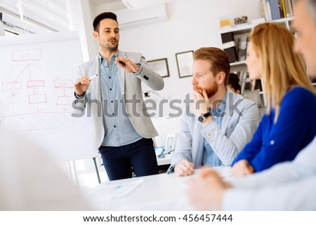 Businesspeople collaborating and talking through new ideas in office - stock photo