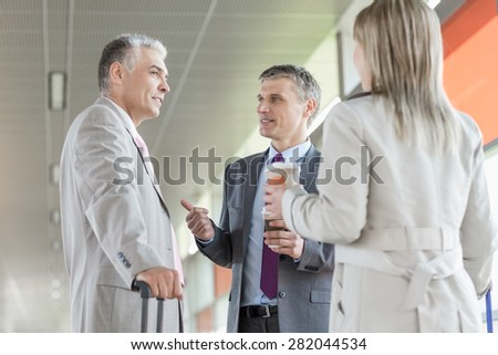 Businesspeople communicating on railroad platform