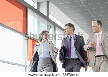 Businesspeople communicating while walking on railroad platform - stock photo