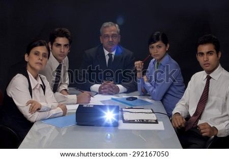 Businesspeople concentrating on projection presentation - stock photo