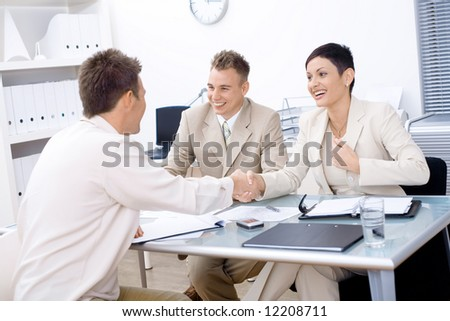 Businesspeople conducting job interview in brightly lit office. - stock photo