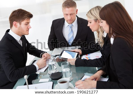 Businesspeople discussing at desk in meeting at office