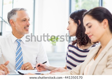 Businesspeople discussing at desk in the office - stock photo
