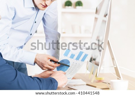 Businesspeople discussing business graph in office - stock photo