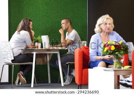 Businesspeople discussing while sitting at table in modern office lobby - stock photo