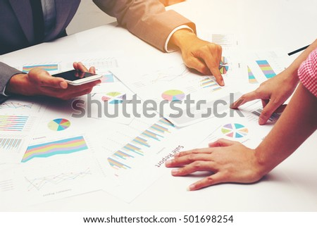 Businesspeople evaluating business reports on table in office
