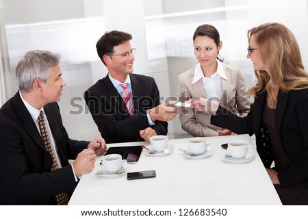 Businesspeople exchanging cards over coffee while having an informal meeting in a cafe - stock photo
