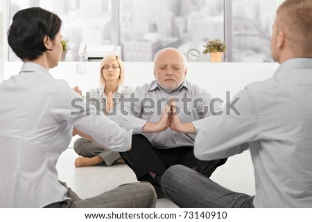 Businesspeople exercising yoga in office with eyes closed, focus on senior businessman.? - stock photo