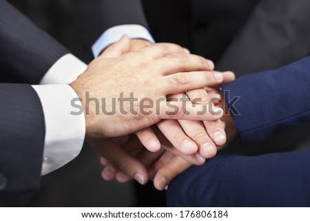 Businesspeople hands on top of each other as symbol of their union - stock photo