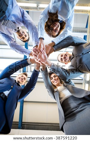 Businesspeople hands stacked over each other in office - stock photo