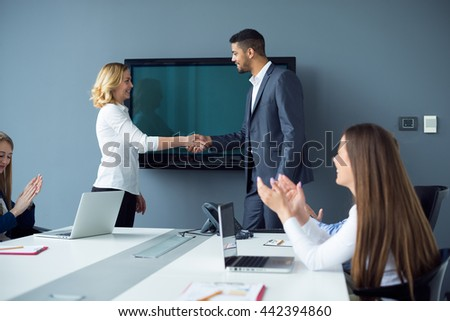 Businesspeople handshaking on a business meeting. Soft focus, high ISO, grainy image. - stock photo