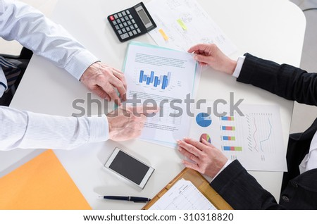 Businesspeople having a discussion about  financial report at office - stock photo