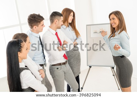 Businesspeople having meeting in a office. Young businesswoman standing  in front of flip chart and having presentation. - stock photo