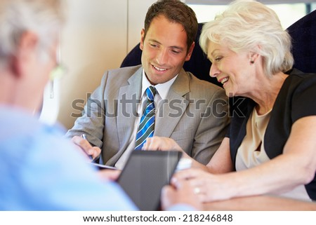 Businesspeople Having Meeting On Train