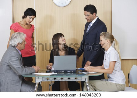 Businesspeople having meeting with laptop in conference room - stock photo