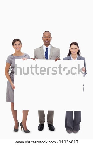 Businesspeople holding blank sign against a white background - stock photo