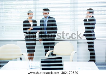 Businesspeople in a meeting at office. View through blinds