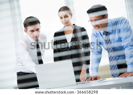 Businesspeople in a meeting at office. View through blinds - stock photo