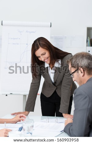Businesspeople in a meeting with an attractive businesswoman standing looking down at documents spread out on a table being discussed by her colleagues - stock photo