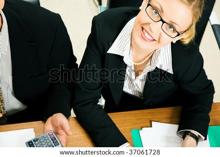 Businesspeople in a team meeting, a woman smiling at the camera - stock photo
