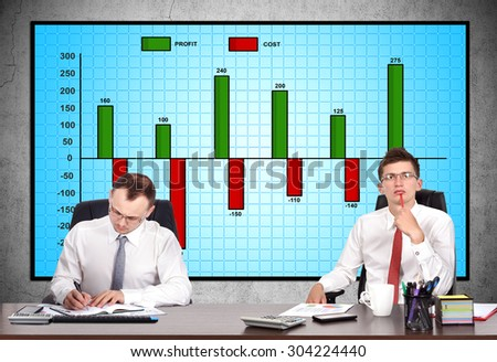 businesspeople in office and cost chart on screen - stock photo