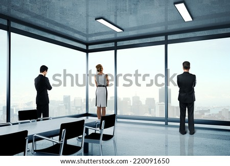 businesspeople in office and looking to window - stock photo