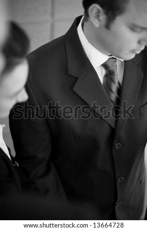 businesspeople in suits all looking down in same direction