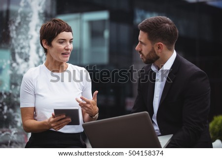 Businesspeople interacting with each other in office building