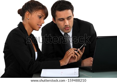 Businesspeople looking at a mobile phone - stock photo