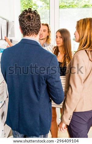 Businesspeople looking at bulletin board in office and discussing designs pinned at it. Mixed caucasian group rather casual, might be a startup comany or a creative agency.  - stock photo