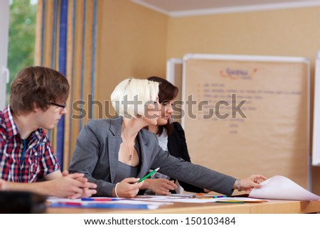 businesspeople looking at documents in a meeting - stock photo