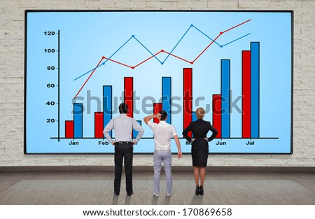businesspeople looking at plasma panel with chart - stock photo
