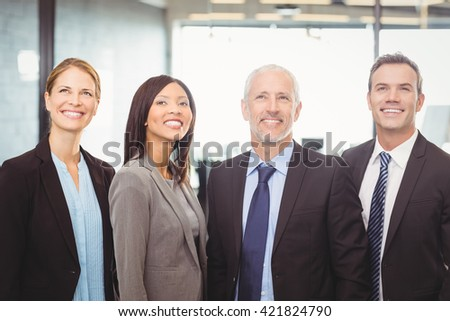 Businesspeople looking up and smiling in office - stock photo