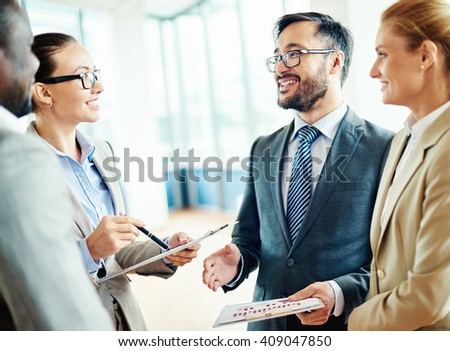 Businesspeople of two organizations meeting and discussing a deal - stock photo
